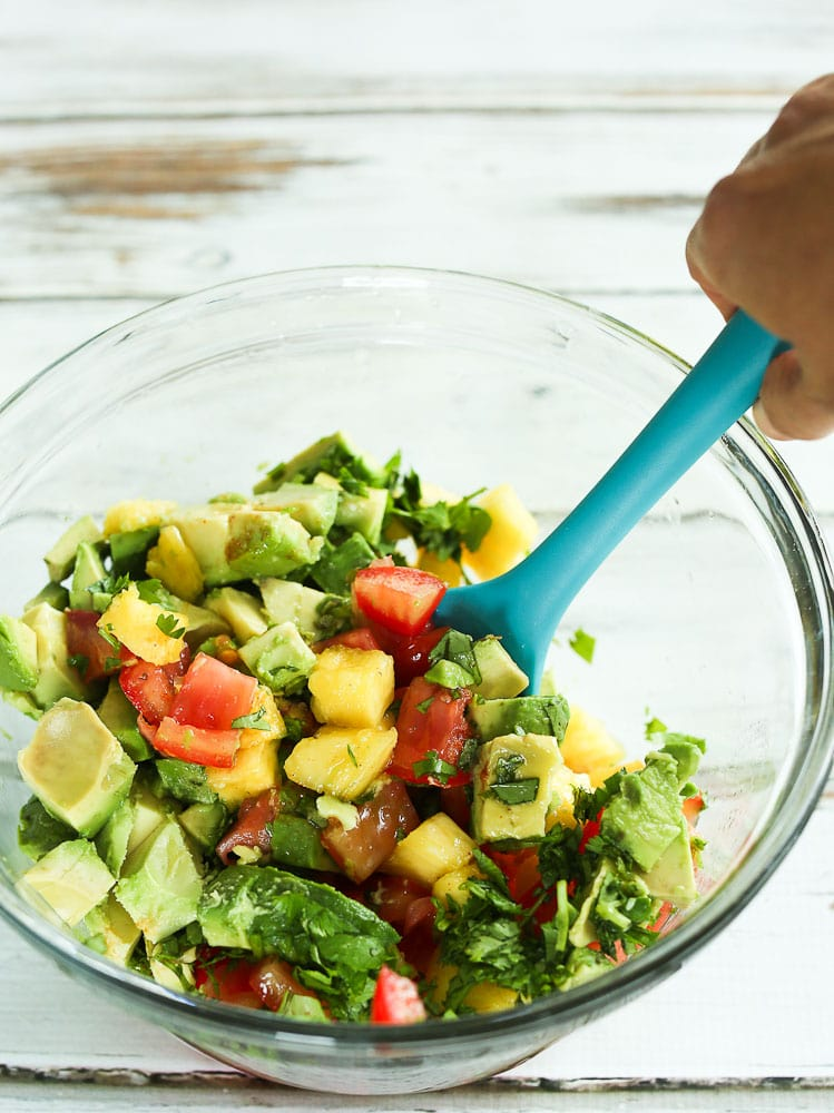 ingredients for pineapple avocado salsa in a bowl with a spoon