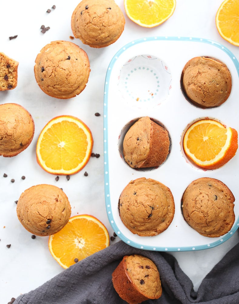 Orange Chocolate Chip Muffins-on a table with orange slices and chocolate chips healthy muffin recipeOrange Chocolate Chip Muffins-on a table with orange slices and chocolate chips healthy muffin recipe
