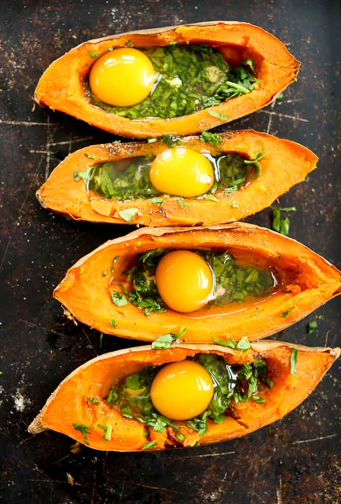 Step 3 of preparing Baked Eggs with Spinach in sweet potato boats--raw eggs added