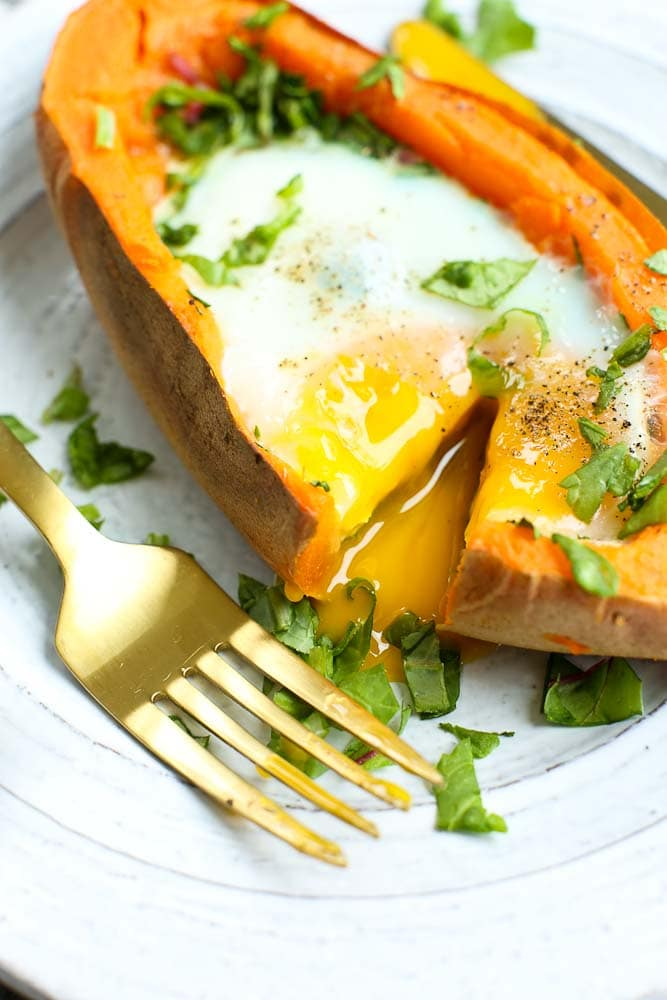 Runny yolk baked egg with spinach stuffed inside a sweet potato