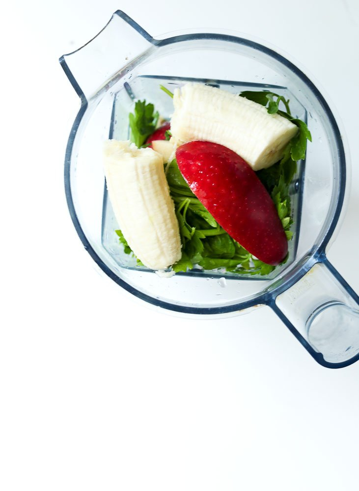 top of blender Ingredients for the Wake Me Up Green Smoothie Recipe (parsley, lime, apple, spinach cube)