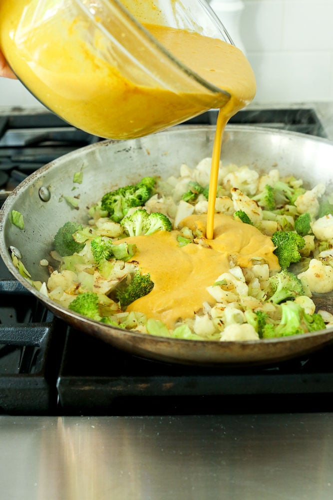 Sauce being poured over vegetables for Vegetable Pumpkin Curry Recipe