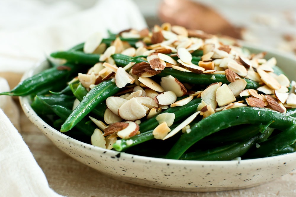 Garlic Butter Green Beans recipe with toasted almonds in a bowl and a cream napkin