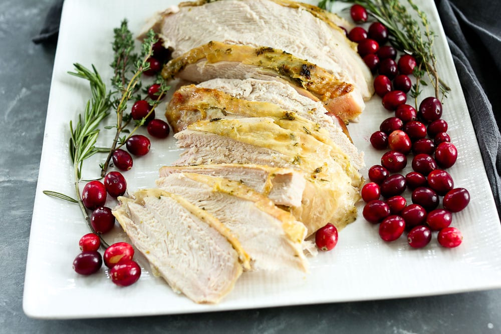 Roasted Turkey Breast recipe--on a plate with fresh cranberries and rosemary