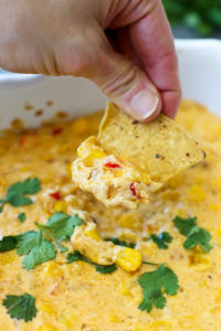 Hot Corn Dip Recipe-close up of taking a chip into the cheesy dip