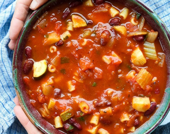 Minestrone Soup Recipe in a bowl with two hands around the bowl