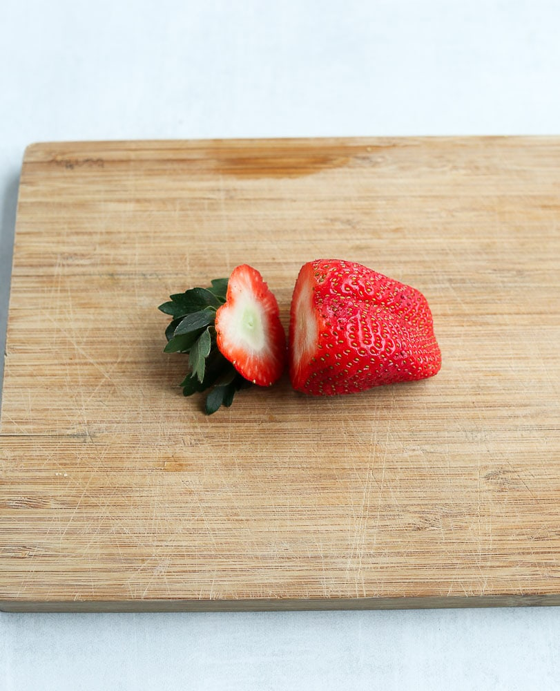 cut the top off of the strawberry to make a strawberry heart