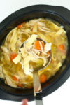 crockpot chicken noodle soup recipe ladle with soup coming out of pot