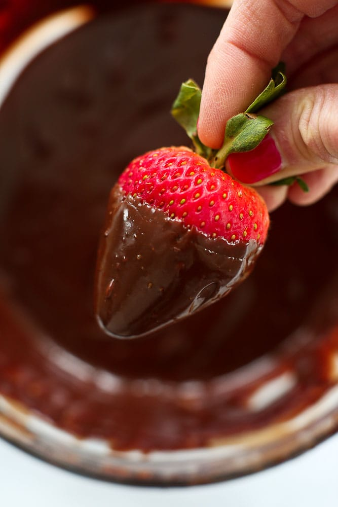 how to make vegan chocolate ganache-using it to dip a strawberry